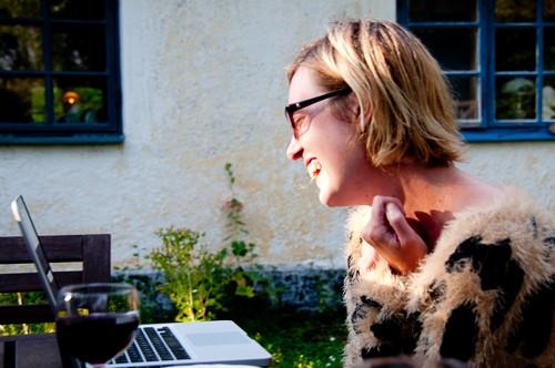 jag som skrattar med rödvin framför datorn